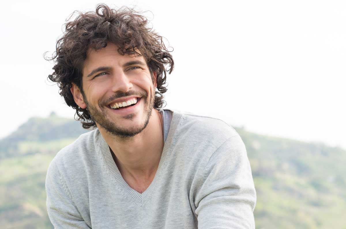 Man with curly hair looking up and smiling